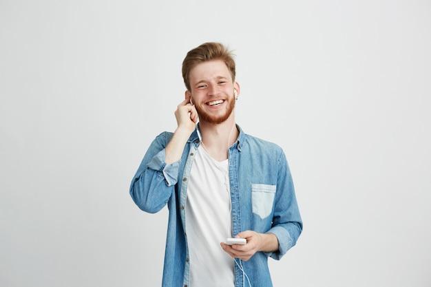 Cara alegre jovem em fones de ouvido, sorrindo, segurando o telefone ouvindo música.