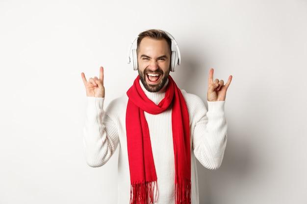 Cara alegre ouvindo heavy metal em fones de ouvido, mostrando um gesto de rock e gritando de alegria, em pé sobre um fundo branco