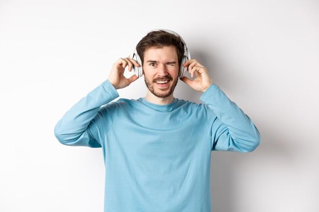 Cara alegre pisca para a câmera e sorrindo, ouvindo música em fones de ouvido sem fio, fundo branco.