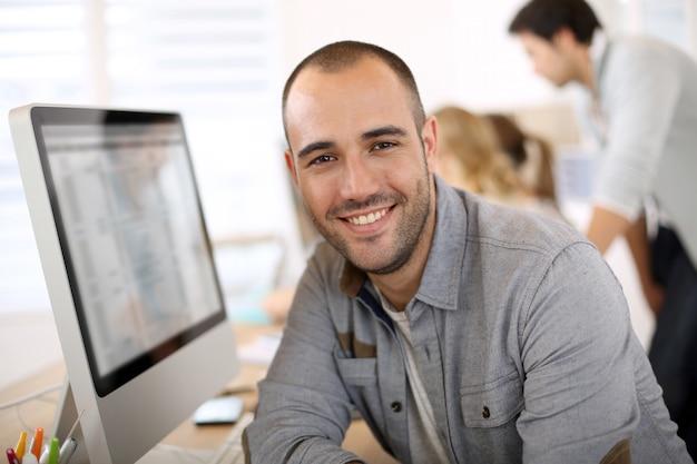 Cara alegre sentado em frente ao computador desktop