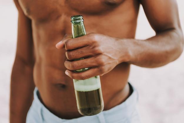 Cara americana em topless americana detém a garrafa de cerveja
