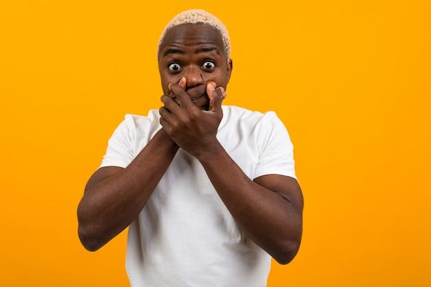 Cara americano surpreso bonito em uma camiseta branca fecha a boca com as mãos de surpresa em amarelo isolado