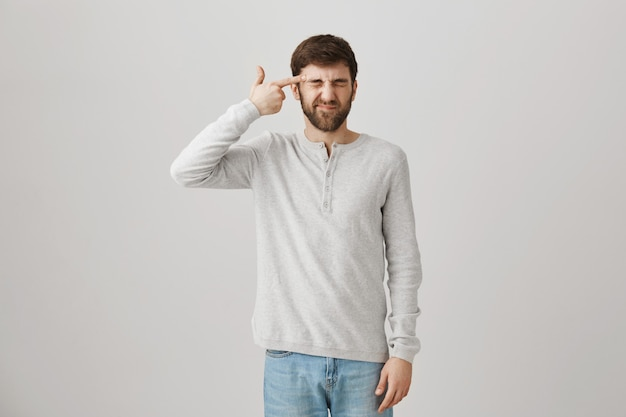 Cara angustiado e incomodado fazendo gesto de arma perto da cabeça