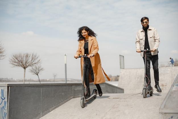 Cara anindian garota europeia andar de scooters e sorrir.