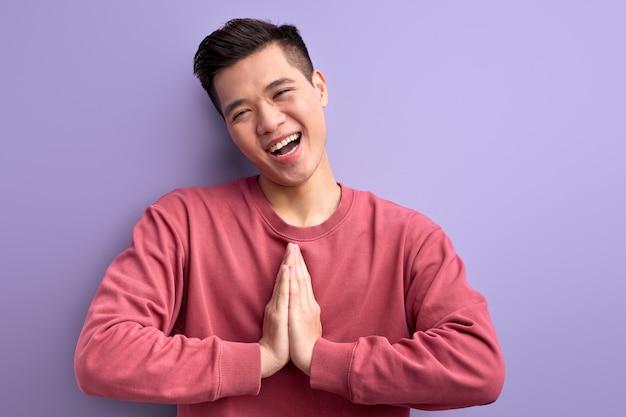 Cara asiática positiva mantendo as mãos juntas, sorrindo. jovem homem casual olhando para a câmera com um sorriso alegre