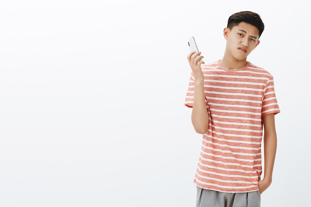 Cara asiático adolescente legal, mandão e sério, em uma camiseta listrada, levando o smartphone como se distraído.