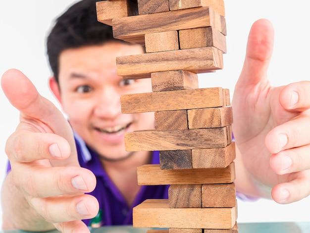 Cara asiático está jogando jenga, um jogo de torre de blocos de madeira