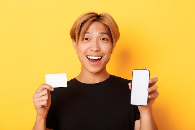 Cara asiático feliz espantado, mostrando o cartão de crédito e a tela do smartphone, sorrindo, fascinado, em pé a parede amarela.