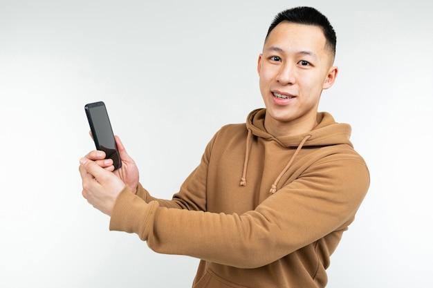 Cara asiático mostra um smartphone na mão em um branco