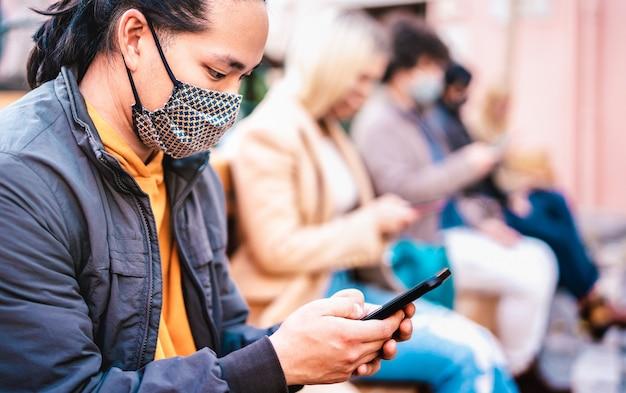 Cara asiático usando smartphone coberto por máscara facial na segunda onda de covid