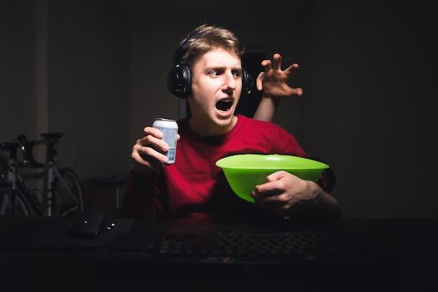 Cara assustada assiste filmes de terror no computador em casa