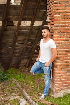 Cara atraente ao lado de uma parede de tijolos