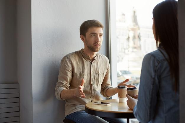 Cara atraente caucasiana, com cabelos escuros e cerdas, sentado no café num encontro conversando com sua namorada sobre seu trabalho, gesticulando com as mãos e tomando café.