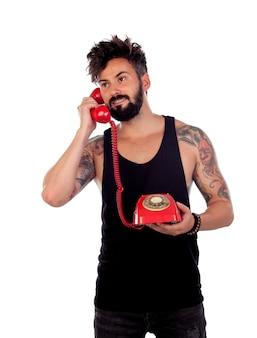 Cara atraente com um velho telefone vermelho