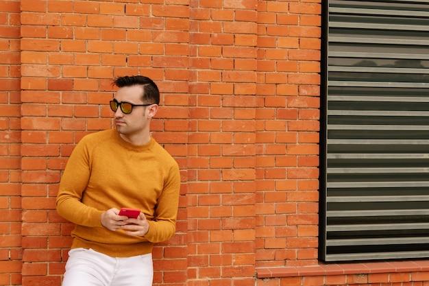 Cara atraente e jovem em óculos de sol laranja usando seu smartphone, vestido com roupas amarelas e paredes de tijolos. conceito de estilo de vida.