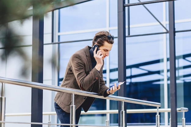 Cara atraente elegante na jaqueta com passaporte de telefone e bilhetes