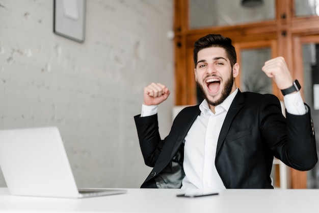 Cara atraente feliz no local de trabalho com o laptop no escritório