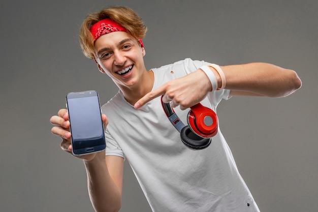 Cara atraente mostra a tela do telefone com uma maquete e fones de ouvido em uma parede cinza
