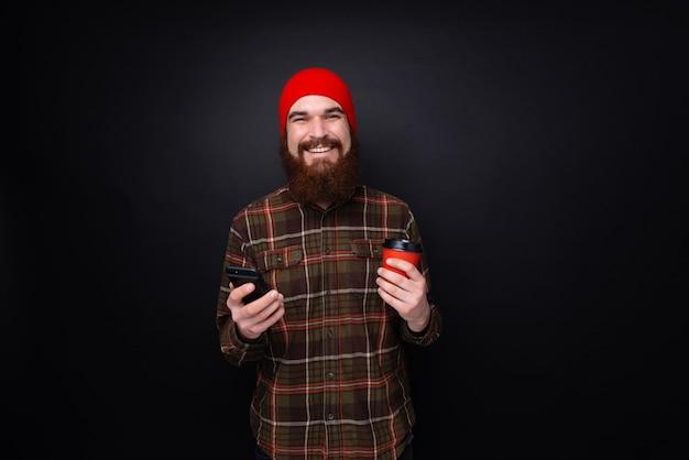 Cara barbudo alegre com chapéu vermelho sorrindo para a câmera enquanto segura uma xícara com café e celular