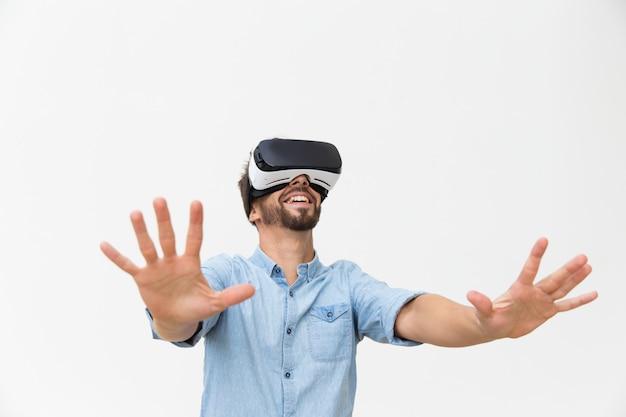 Cara barbudo animado em óculos de realidade virtual, desfrutando de experiência
