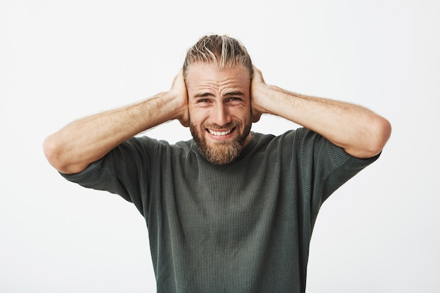 Cara barbudo bonito com penteado elegante fechar as orelhas com as mãos