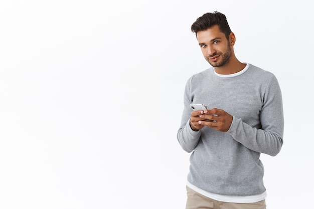 Cara barbudo bonito em suéter cinza segurando um smartphone, olhar a câmera com um sorriso fofo, conversando no aplicativo, usando o aplicativo, parede branca