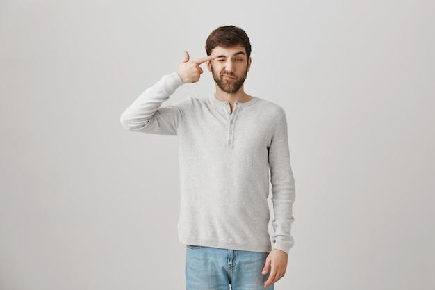 Cara barbudo caucasiano cansado, fazendo gesto de arma perto da têmpora