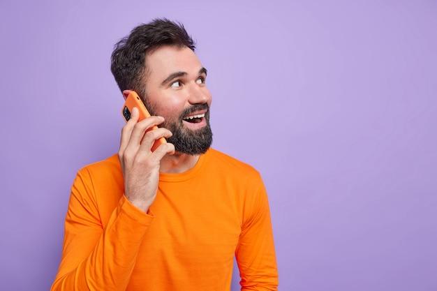 Cara barbudo com expressão alegre expressa emoções sinéquicas fala via smartphone desvia o olhar e conversa alegre vestido com macacão laranja de manga comprida
