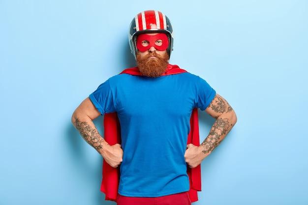 Cara barbudo confiante mantém as mãos na cintura, pronto para a defesa, olha com olhar forte e poderoso diretamente para a câmera, usa capacete