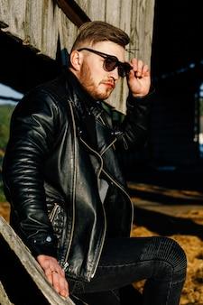 Cara barbudo de óculos escuros em uma jaqueta de couro senta-se no fundo de uma parede de madeira velha
