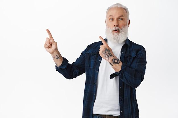 Cara barbudo e tatuado surpreso, apontando para o logotipo promocional do canto superior esquerdo e arfando e surpreso, checando um banner de notícias incrível e empolgante, encostado na parede branca