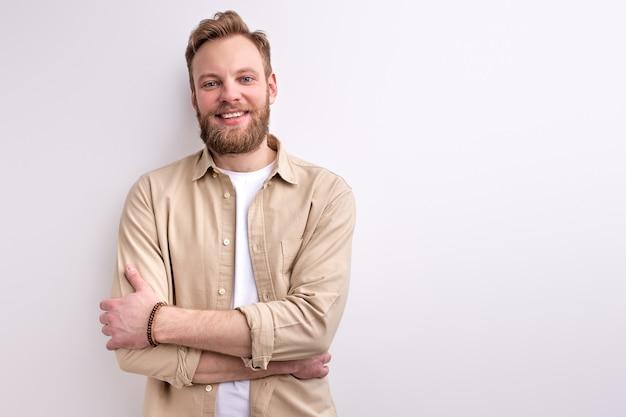 Cara barbudo em roupa casual posando para a câmera com um sorriso agradável e amigável, posando isolado no fundo branco do estúdio