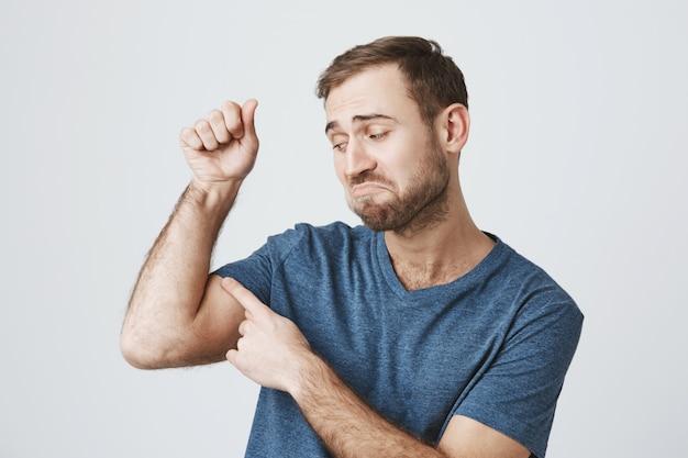 Cara barbudo insatisfeito flexiona os bíceps fracos, sem força