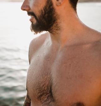 Cara barbudo na praia perto da água no verão