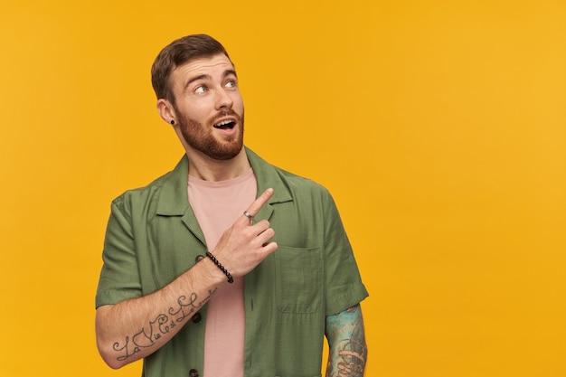 Cara barbudo, olhando curiosamente um homem com cabelo castanho. jaqueta verde de mangas curtas. tem tatuagem. observando e apontando o dedo para a direita no espaço da cópia, isolado sobre a parede amarela