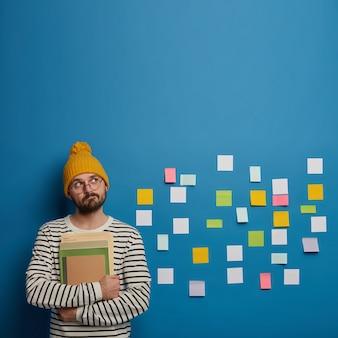Cara barbudo pensativo segura livros, olha pensativamente para cima, pensa em como fazer um projeto, pensa em ideias diferentes