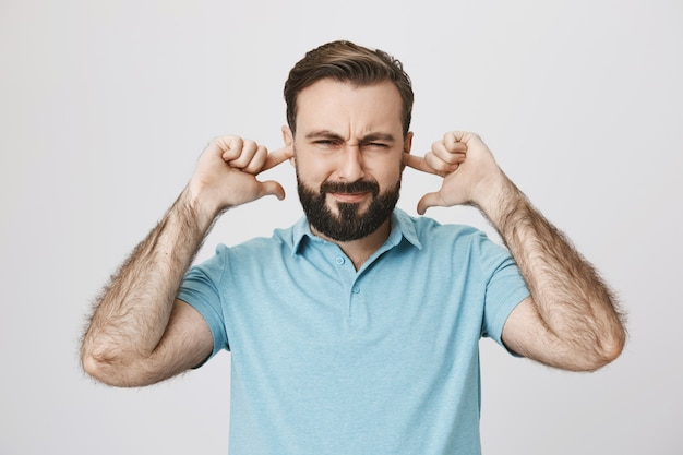 Cara barbudo perturbado fechando as orelhas e apertando os olhos irritado