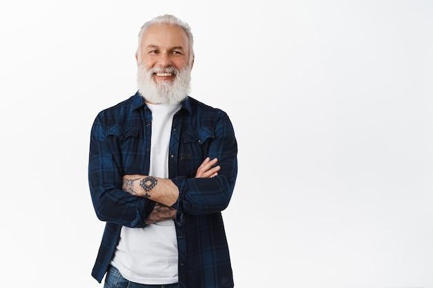 Cara barbudo sênior hippie com tatuagens de braços cruzados no peito, parecendo determinado e feliz na frente, em pé sobre uma parede branca