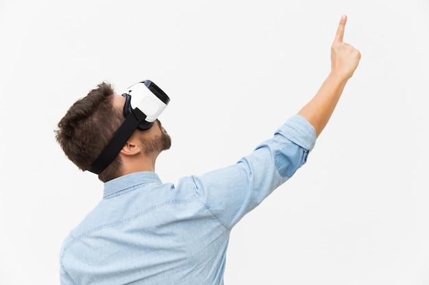 Cara barbudo usando óculos de realidade virtual, apontando o dedo para cima