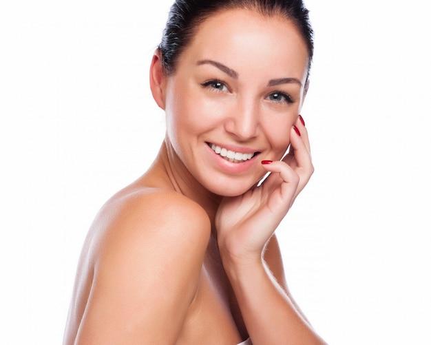 Cara bonita da mulher de sorriso bonita - levantando no estúdio isolado no branco