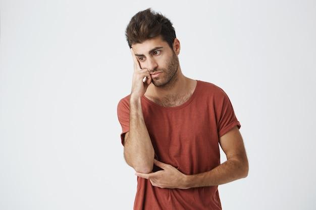 Cara bonita de barba por fazer latino-americano em camiseta vermelha mal-humorado, olhando de lado, segurando a mão na testa chateado com a briga com o amigo.