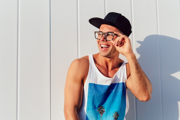 Cara bonito alegre em óculos posando perto da parede urbana, vestindo camiseta sem mangas