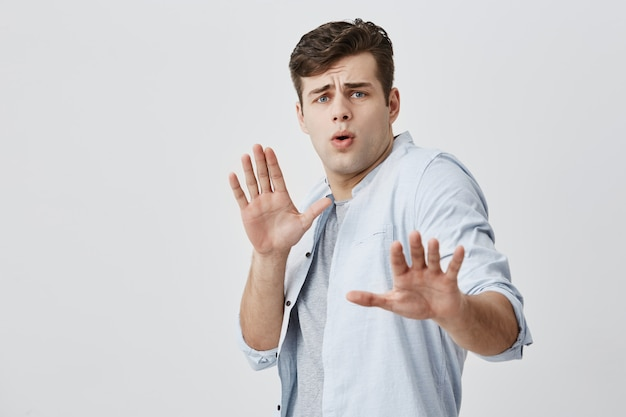 Cara bonito caucasiano melindroso, com cabelos escuros, mostrando o sinal de stop com as palmas das mãos, enquanto sua garota tentando acusá-lo de algo. jovem assustado exclamando e franzindo a testa