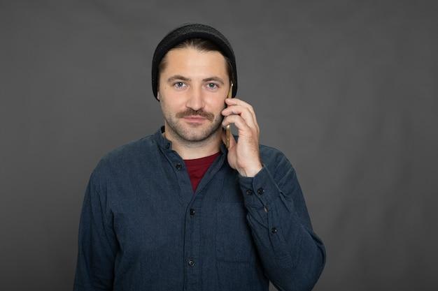 Cara bonito com a barba por fazer e boné de malha falando no telefone em estúdio cinza