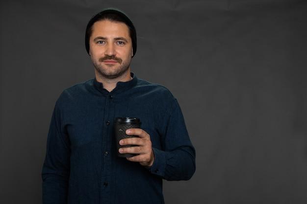 Cara bonito com a barba por fazer e boné de malha posando com copo descartável em estúdio cinza