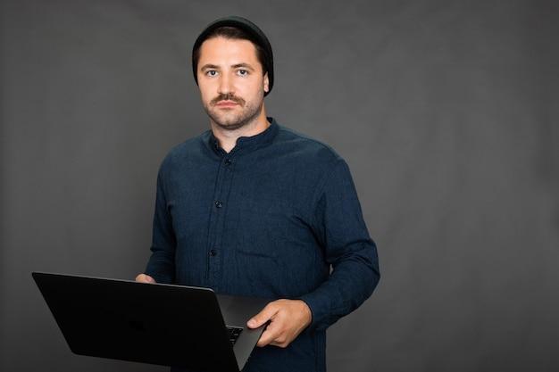 Cara bonito com a barba por fazer e boné de malha posando com o laptop no estúdio cinza