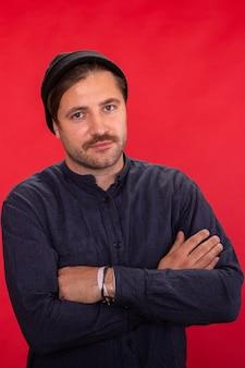 Cara bonito com a barba por fazer e boné de malha posando de braços cruzados sobre o cenário vermelho