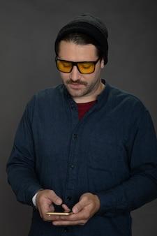 Cara bonito com a barba por fazer e boné de malha segurando um smartphone e fazendo uma ligação de celular