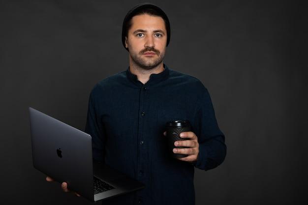 Cara bonito com a barba por fazer segurando um laptop e uma xícara de café descartável no estúdio cinza Foto Premium