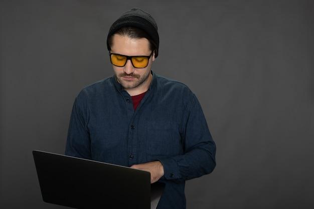 Cara bonito com a barba por fazer trabalhando com o laptop no espaço de cópia do estúdio cinza